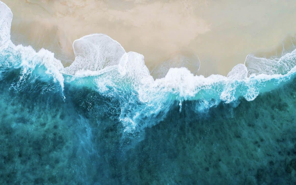 Drone image of the ocean touching a beach and it's a beautiful, rich turquoise color